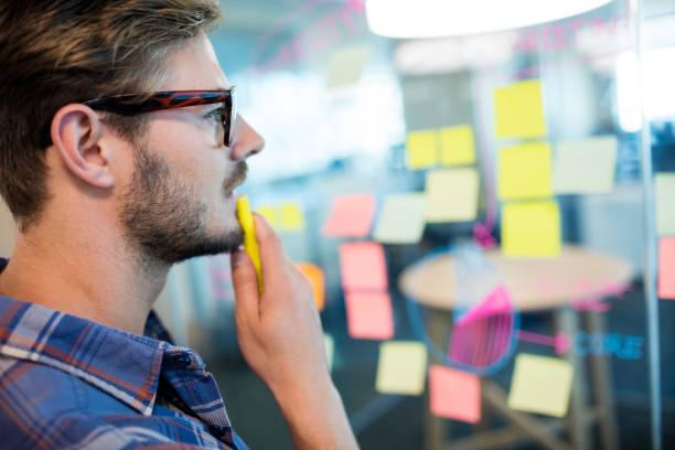 hombre pensativo leyendo notas adhesivas en la pared de vidrio - design thinking fotografías e imágenes de stock