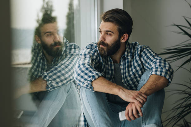 Thoughtful man relaxing on window sill at home. Young pensive man sitting by the window sill and looking through it. one man only stock pictures, royalty-free photos & images