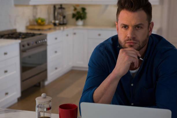 nachdenklicher mann mit laptop am tisch sitzen - schwarzer kaffee net stock-fotos und bilder