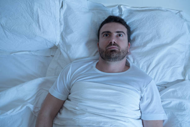 thoughtful man trying to sleep in his bed at night - waking up stock pictures, royalty-free photos & images