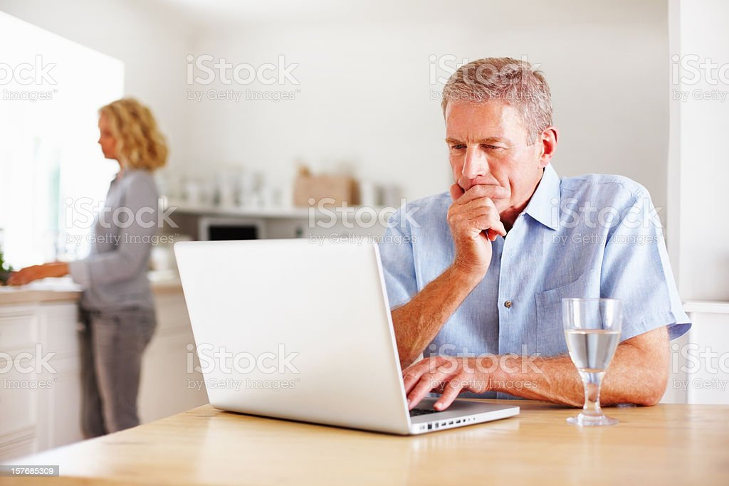 Thoughtful man using laptop while woman cooking in kitchen royalty-free stock photo