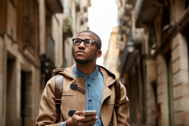 Thoughtful man using mobile phone amidst buildings Thoughtful man using mobile phone. Young male tourist is standing amidst buildings. He is wearing leather jacket. amidst stock pictures, royalty-free photos & images