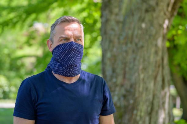 Thoughtful man wearing a fashionable face guard stock photo