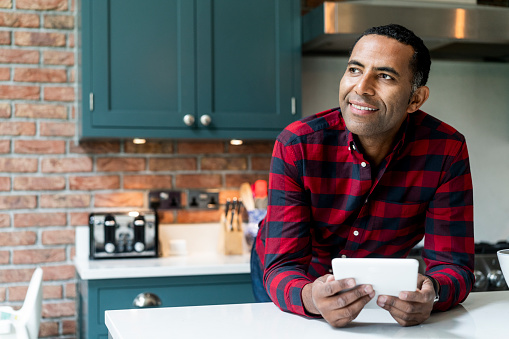 Thoughtful mature man leaning on kitchen island. Smiling male is holding digital tablet while standing in kitchen. He is in red checked shirt at home.