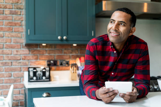 Thoughtful man with digital tablet in kitchen stock photo