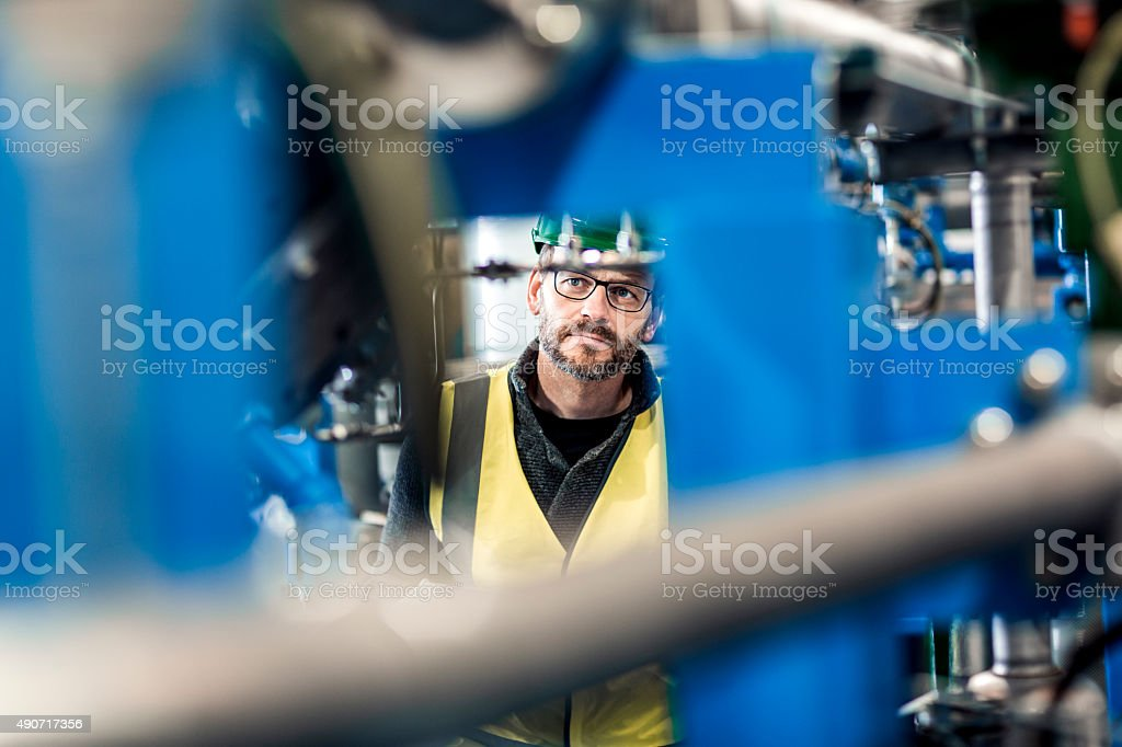 Thoughtful manual worker analysing machines in factory stock photo
