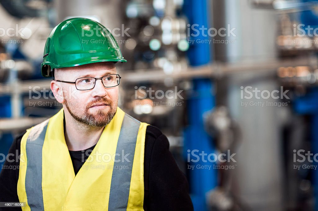 Thoughtful manufacturing professional standing in factory stock photo
