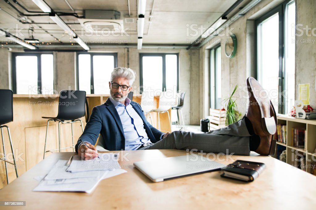 Thoughtful mature businessman in the office. stock photo