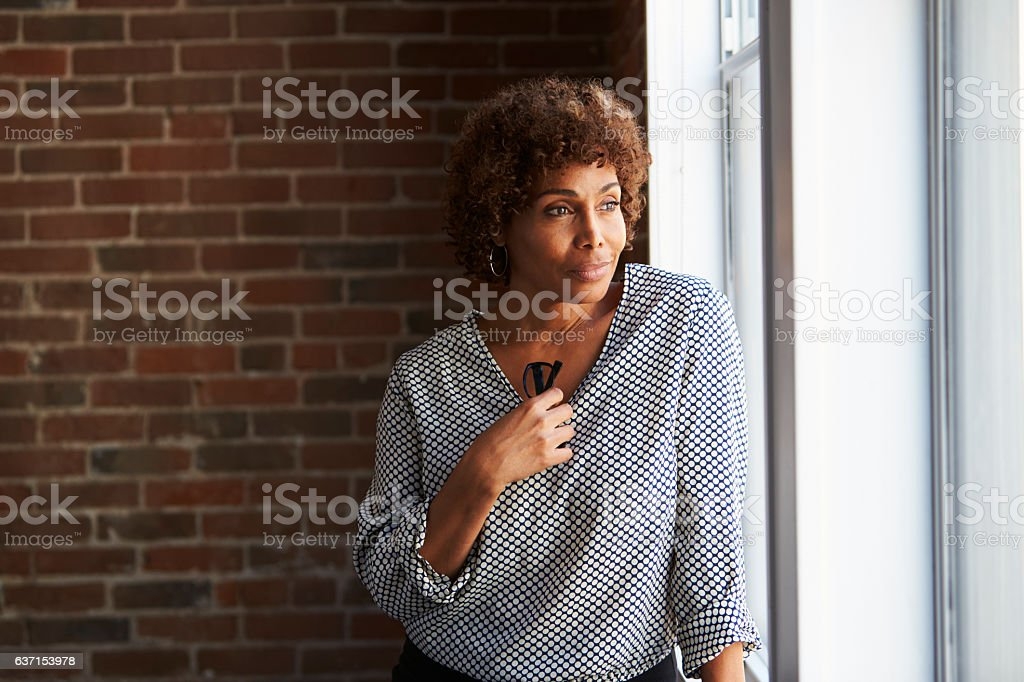 Thoughtful Mature Businesswoman Looking Out Of Office Window stock photo