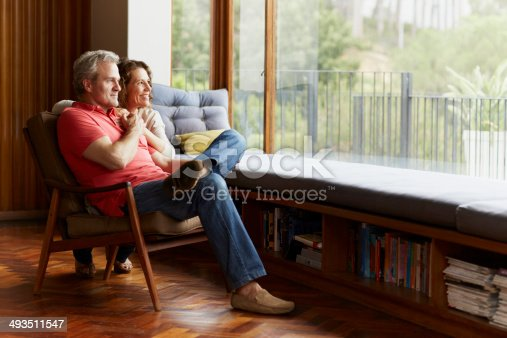 Thoughtful mature couple relaxing by window at home