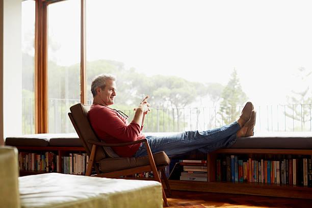 thoughtful mature man relaxing on armchair - lässiges wohnzimmer stock-fotos und bilder