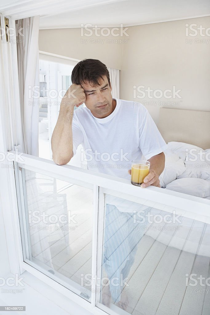 Thoughtful mature man with an orange juice at a window royalty-free stock photo