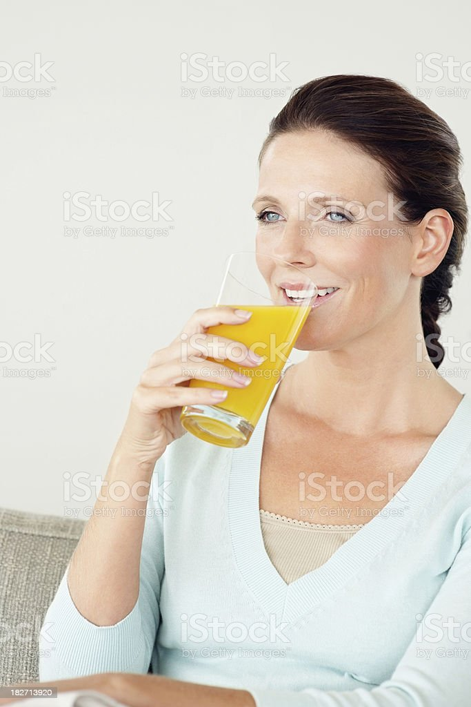 Thoughtful mature woman drinking a glass of juice royalty-free stock photo