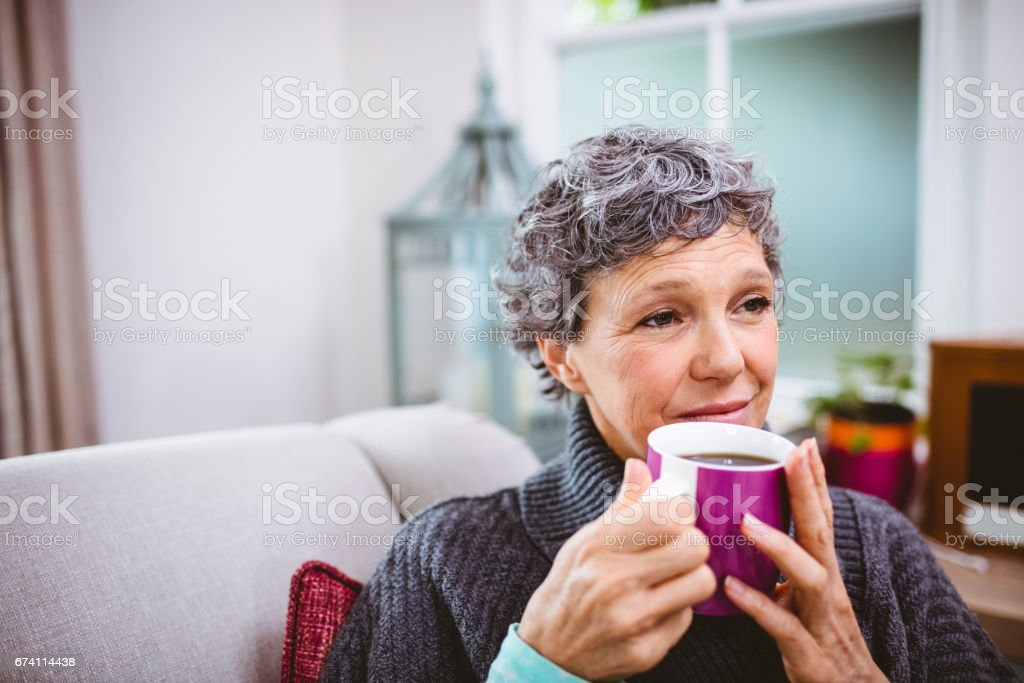 Thoughtful mature woman holding coffee cup royalty-free stock photo