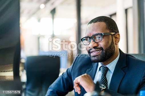 Thoughtful mid adult businessman sitting at creative workplace. Male professional is day dreaming while looking away. He is wearing suit.