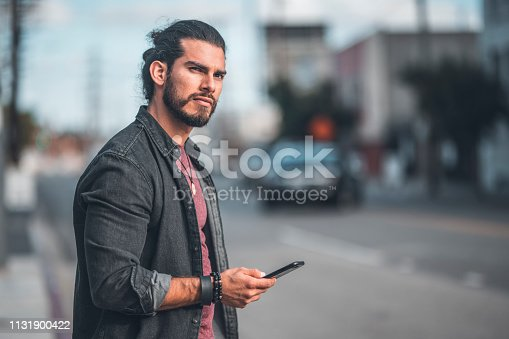 Confident mid adult man holding smart phone. Thoughtful fashionable male is standing in city. He is wearing casuals.