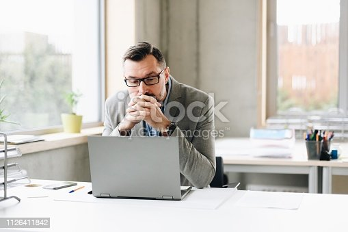 Thoughtful middle aged handsome businessman in shirt working on laptop computer in office. Man working in office