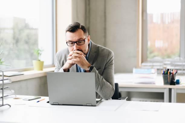 Nachdenklich mittleren Alter schön Geschäftsmann im Hemd auf Laptop-Computer im Büro arbeiten – Foto