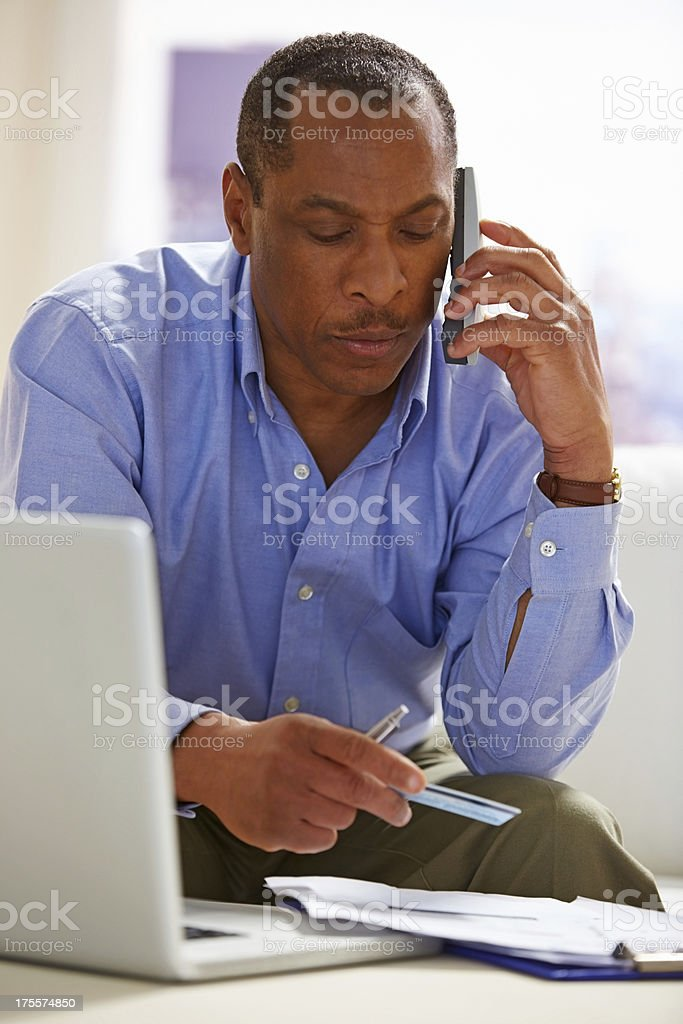 Thoughtful middle aged man with credit card talking on phone royalty-free stock photo