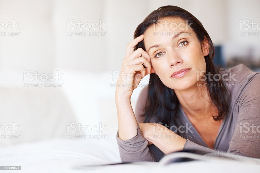 Thoughtful middle aged woman with book - copyspace royalty-free stock photo