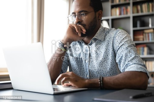 Thoughtful millennial biracial man in eyeglasses stack with hard task, looking at laptop screen. Puzzled young african ethnic businessman thinking of problem solution, making difficult decision.