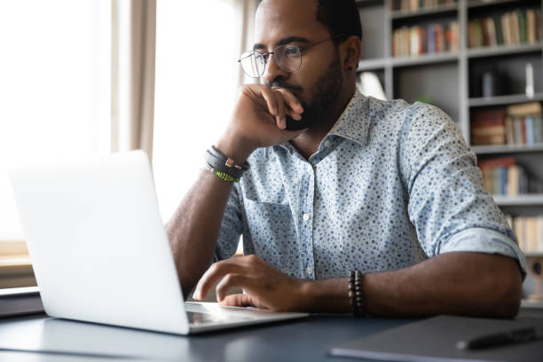 Thoughtful millennial biracial man in eyeglasses stack with hard task. Thoughtful millennial biracial man in eyeglasses stack with hard task, looking at laptop screen. Puzzled young african ethnic businessman thinking of problem solution, making difficult decision. investor stock pictures, royalty-free photos & images