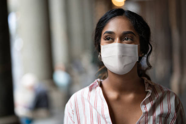 Thoughtful mixed-race woman on the street wearing a facemask stock photo
