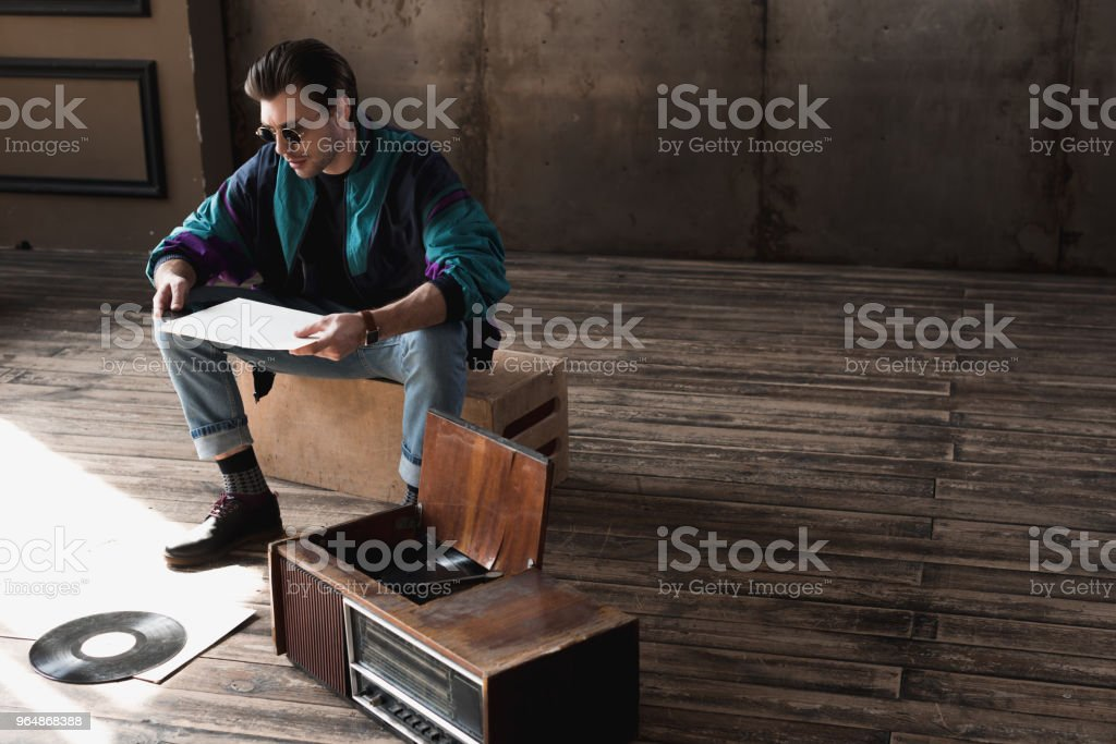 thoughtful nostalgic man in vintage windcheater with vinyl record player royalty-free stock photo