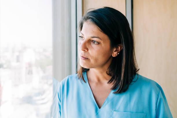Thoughtful nurse by window in hospital stock photo