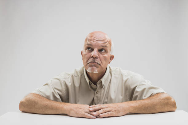 Thoughtful older balding man sitting at a table stock photo