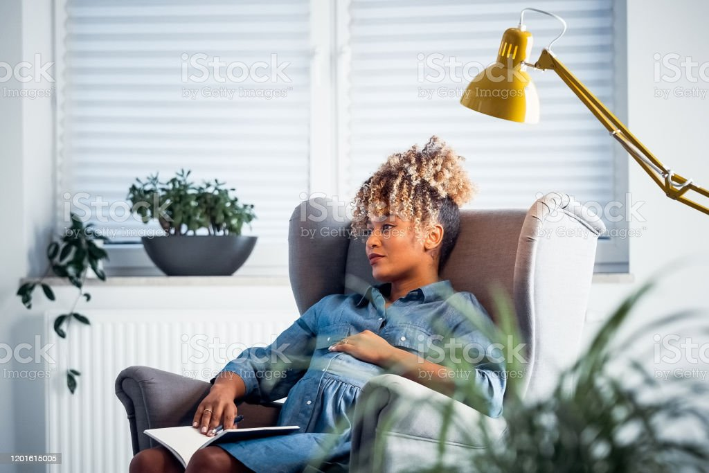 Thoughtful pregnant owner resting in new office Thoughtful businesswoman looking away while sitting on armchair. Pregnant owner is resting in new office. She is having curly and highlighted hair. 35-39 Years Stock Photo