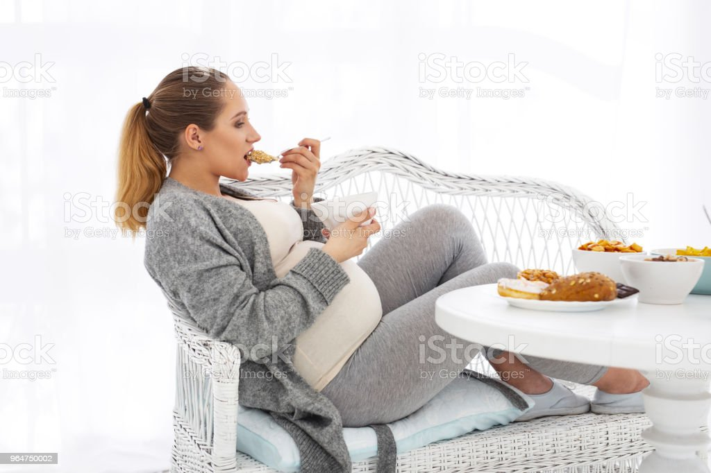 Thoughtful pregnant woman munching granola royalty-free stock photo