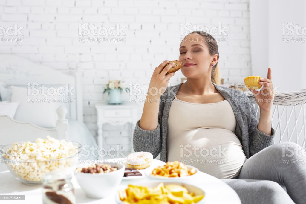 Thoughtful pregnant woman smelling bun royalty-free stock photo