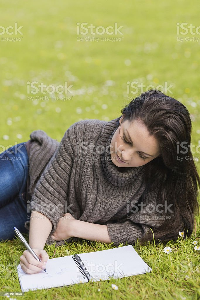 Thoughtful pretty brunette writing while lying on the grass royalty-free stock photo