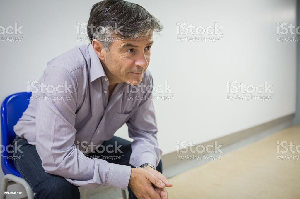 Thoughtful professor sitting on chair royalty-free stock photo