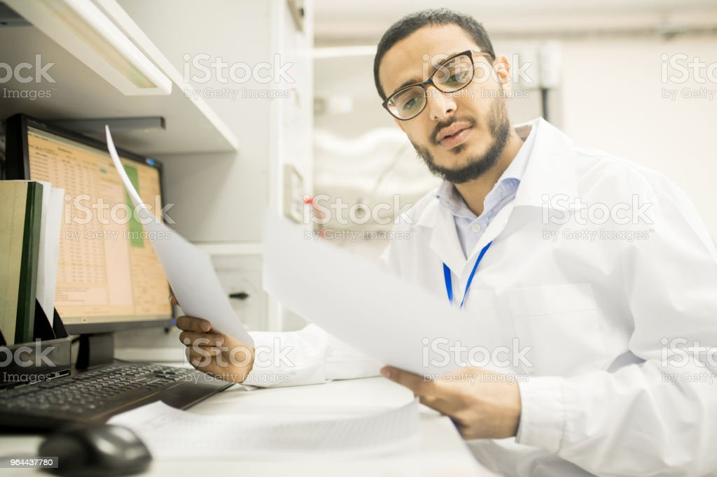 Thoughtful quality control engineer examining data - Royalty-free Adult Stock Photo