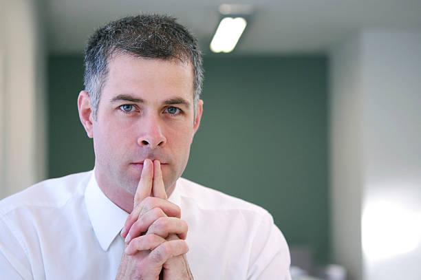 Thoughtful reassuring businessman stock photo