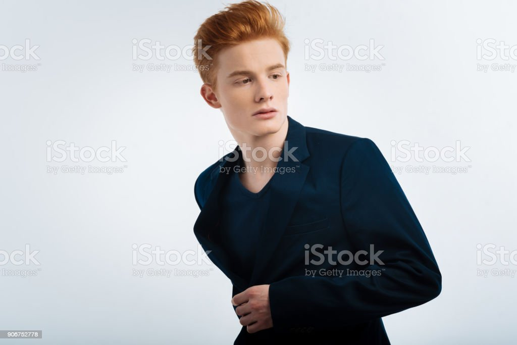 Thoughtful red-haired man buttoning up his jacket stock photo