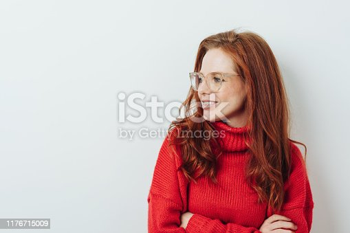 Thoughtful redhead woman with folded arms looking off to the side with a quiet smile against a white wall with copy space