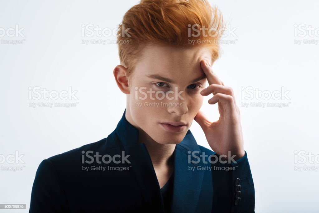 Thoughtful red-headed young man thinking stock photo