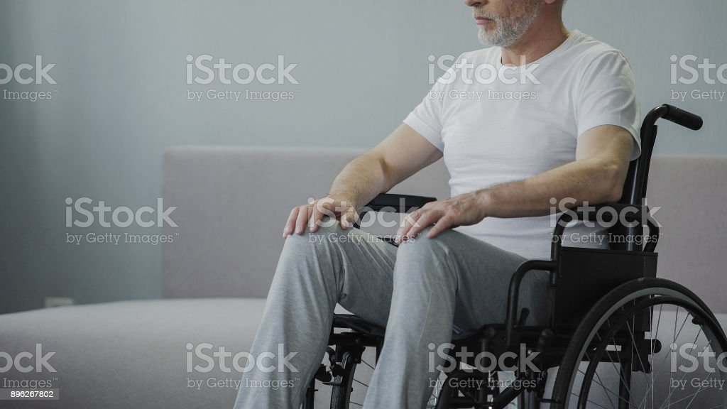 Thoughtful retired male sitting in wheelchair stock photo