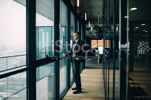 Senior businessman in suit looking out of window