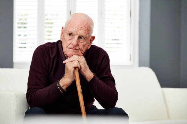 Thoughtful senior man at home Portrait of senior man sitting on couch with a walking stick and thinking at home one senior man only stock pictures, royalty-free photos & images