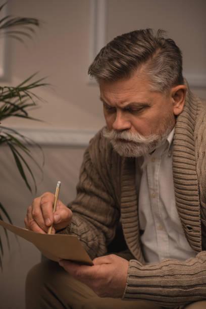 nachdenklicher senior mann in pullover brief schreiben - gedichte zum ruhestand stock-fotos und bilder