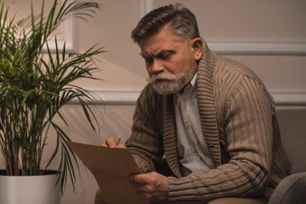 nachdenklicher senior mann in pullover brief beim sitzen im sessel - gedichte zum ruhestand stock-fotos und bilder