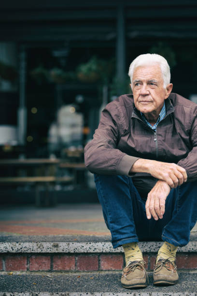 Thoughtful senior man looks depressed as he sits in the street stock photo