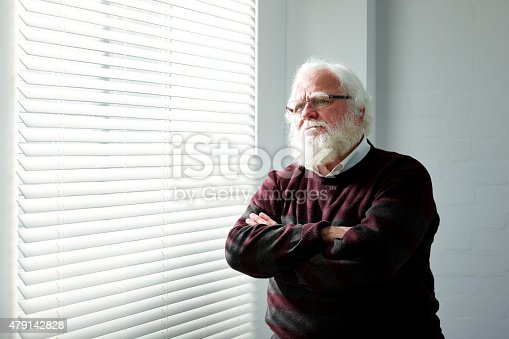 istock Thoughtful senior man standing by a window 479142828