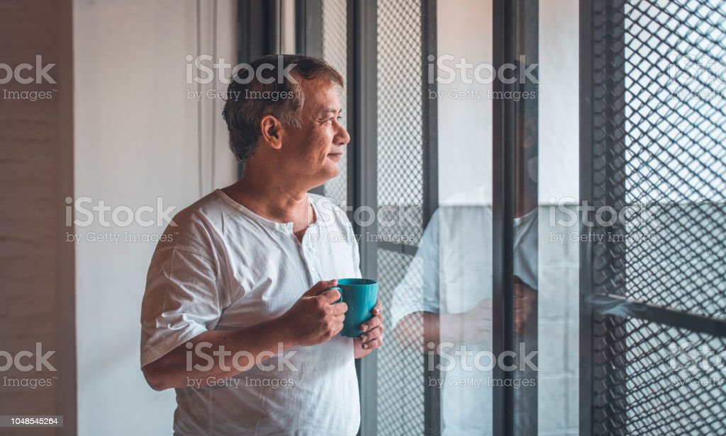 Thoughtful senior man with coffee cup by window stock photo
