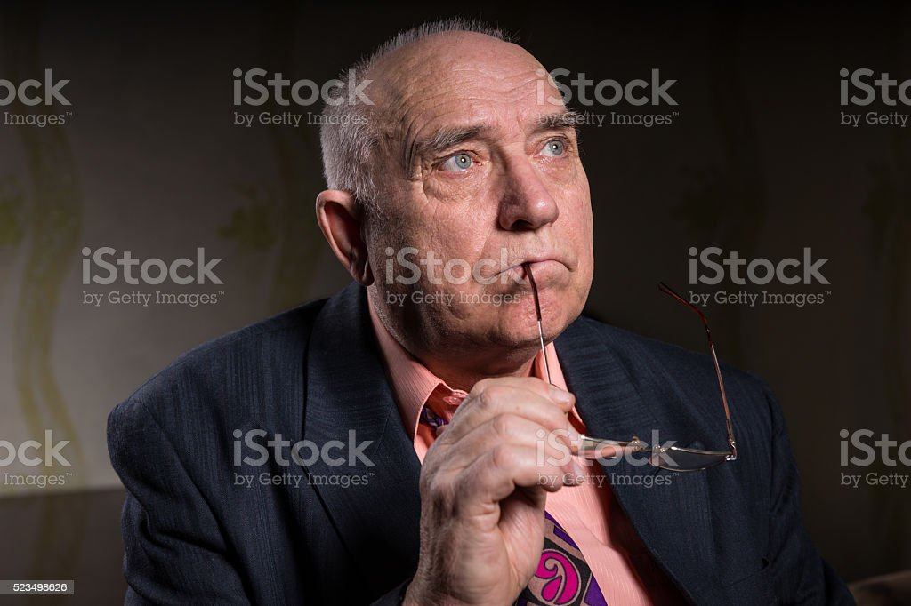 Thoughtful senior man with glasses in his hand stock photo