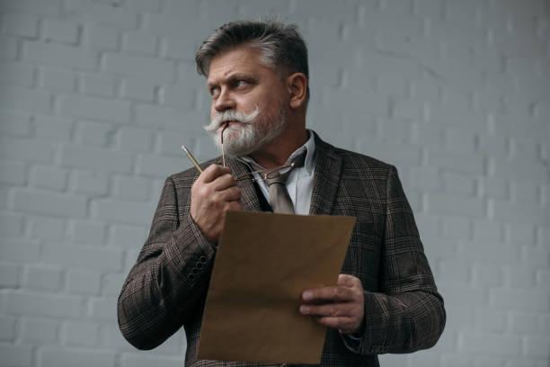 nachdenklicher senior mann mit stift und blatt papier wegschauen - gedichte zum ruhestand stock-fotos und bilder